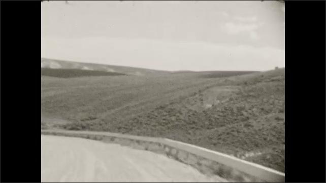 1930s: Large bird flying, mountain on horizon. Bird on fencepost. Bird flying. Driving down road on side of hill. Driving down road, mountain on horizon. Driving, train passes.