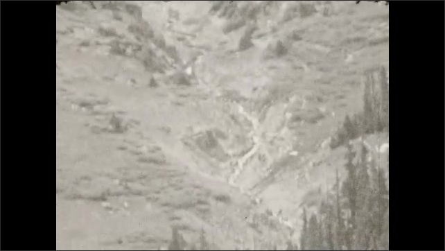 1930s: Trees, valley. Car drives on a mountain road.