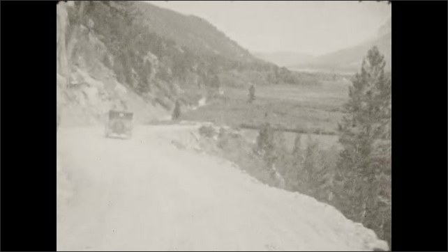 1930s: Woman and girl walk along path in forest. Car drives down mountain road towards large wooden entrance gate.