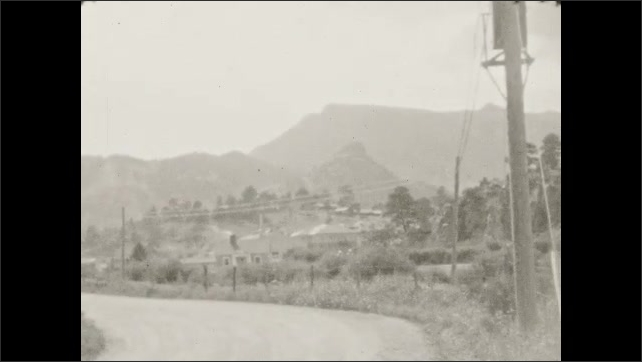 1930s: Buildings at base of mountains. Meadows at base of mountains.