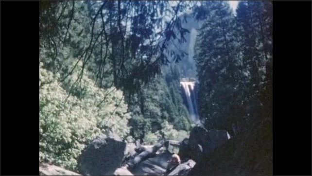 1940s: A boy sits on the ground in front of tree trunk and yawns. Waterfall at a distance surrounded by trees, a man walks on the rocks without a shirt.