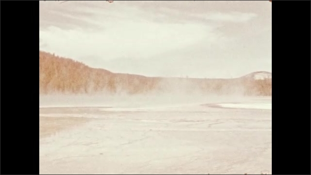 1940s: Young man walks along edge of hot spring.  Steam rises off water.