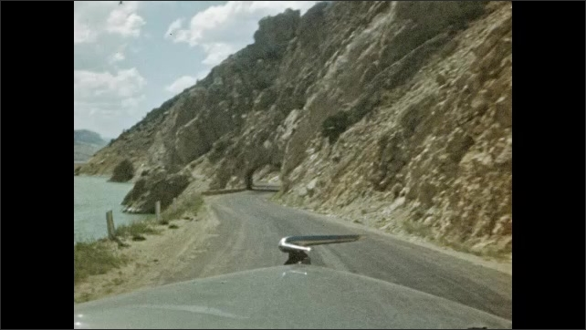 1940s: UNITED STATES: view along road through car windscreen. Car drives through rock tunnels. Drive by lake