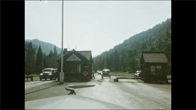 1940s: UNITED STATES: car drives along mountain road. Car arrives at border. Man walks across road.
