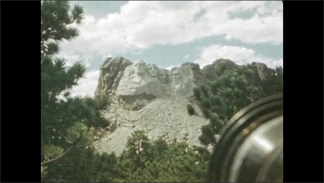 1940s: UNITED STATES: trees by road side. View of road from car window. Faces carved into rocks in cliff. Mount Rushmore Carvings
