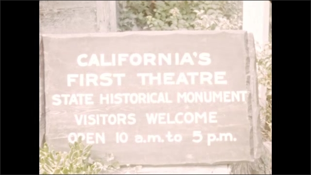 """1940s: Wind blows USA flag. Sign """"California's First Theatre"""". Wind blows USA flag, trees in background. Sign """"First Theatre in California""""."""