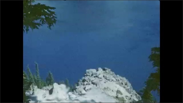 1940s: UNITED STATES: mountains by water. Rocky outcrop in forest.