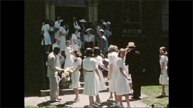 1940s: UNITED STATES: guests at special event by building. Ladies in white dresses. Girl looks at camera.