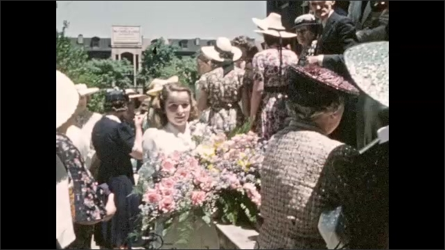1940s: UNITED STATES: ladies gather on steps at event. Girl holds flowers. Ladies look at camera.