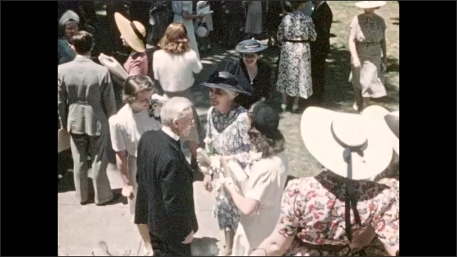 1940s: UNITED STATES: guests gather after celebration. Man shakes hands with lady. Flowers in garden.
