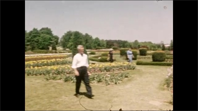 1940s: Large formal garden, long bed of dense pink flowers. Beds of flowers and colorful tulips, neatly trimmed shrubs, low hedges, trees, grass pathways, people walk. Lake, large white house, barn.