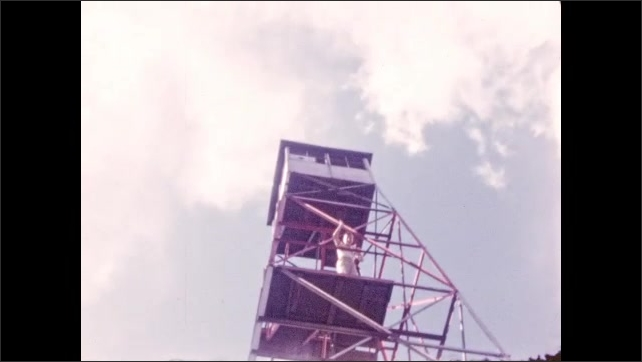 1940s: Boy waves, climbs up stairs of fire tower, waves from higher level, looks proud, shakes clasped hands, celebrates success. View across forested landscape, mountains.