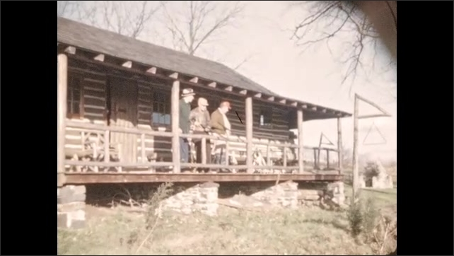1940s: Cows stand and lay near fence. Calf stands up from ground. Men and dog stand on porch of log cabin. Fire roars in fireplace.