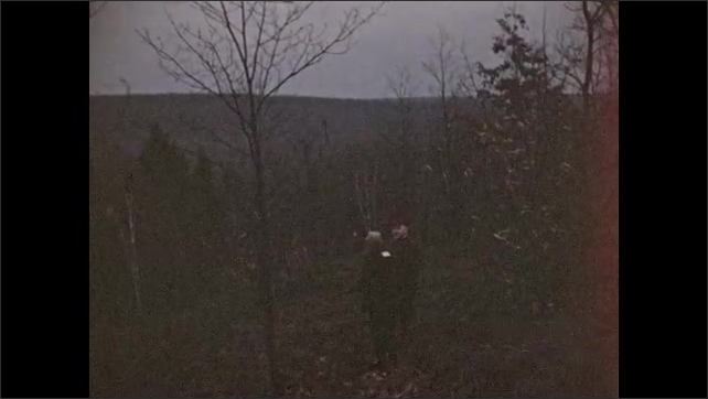 1940s: Man and boy with guns stand on wooded trail. Hunters walk along wooded hillside. Hunters walk down wooded trail.