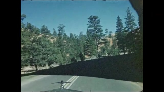 1940s: View from inside car that drives on road and passes through rock tunnels several times, road surrounded by trees.