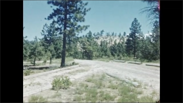1940s: Car parked with open doors next to pine trees and picnic tables. Clothes hang over the door of the car. Panoramic view of Bryce Canyon.