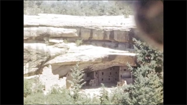 1940s: View out from mountain pueblo. Pueblo windows in rock. Pueblo buildings under mountain rock. View down rock cavern of ruins.
