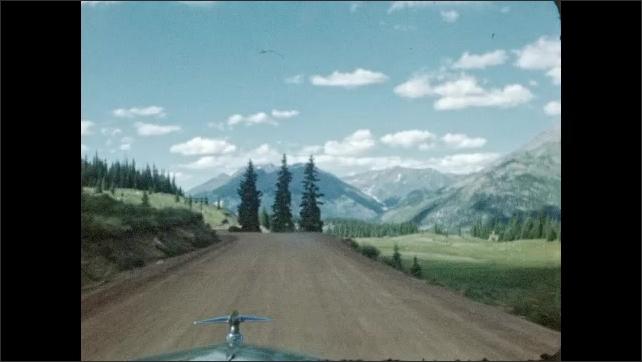 1940s: Car drives down road through mountains.
