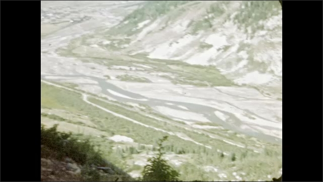 1940s: Car drives down mountain road. Valley, mountains.