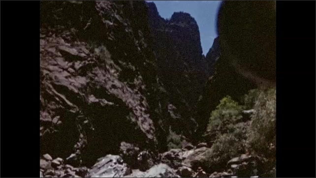 1940s: Man holds pole, stands on rock next to river. Mountains, cliffs. Man walks over rocks.