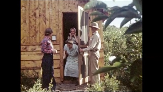 1940s: Canyon, mountains, cliffs. Man stands on rocks at bottom of canyon, waves. Man opens screen door on cabin, three women walk out, pose.