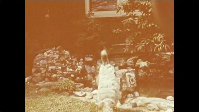 1940s: Dog sits on table, man stands behind fence, watches. Dog sits on rock, jumps down. Dog sits on grass next to small water feature.