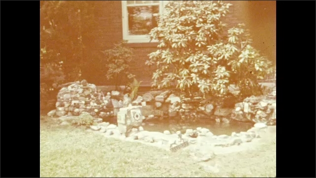 1940s: Dog sits in garden by rocks and water feature.