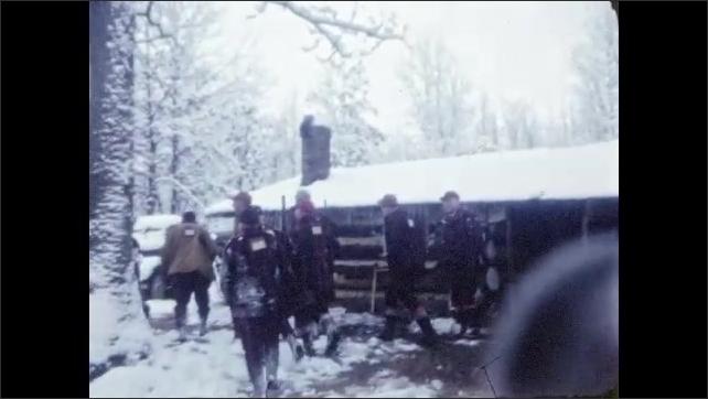 1940s: Barren trees covered in snow. Men with rifles walk near cabin in woods. Men walk through snowy woods.