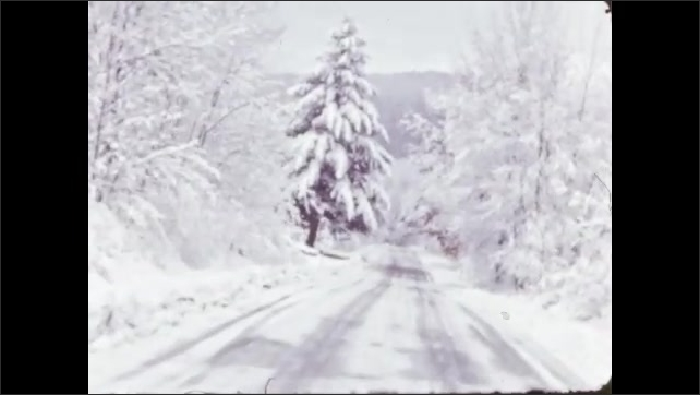 1940s: Car drives along snowy road through woods.