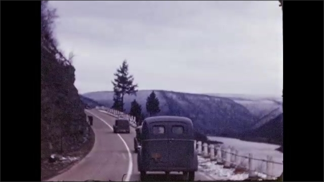 1940s: Cars drive along road by mountain.