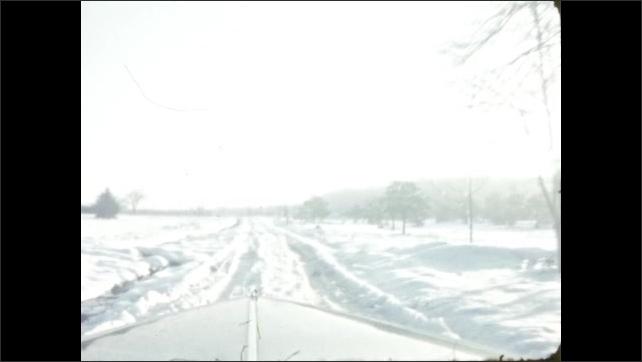 1940s: Car drives through snowy woods.