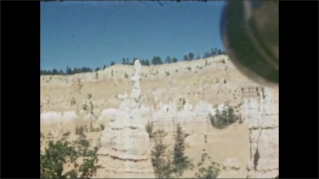 1940s: Hoodoo, rock formations and cliffs in background against blue sky. Sand rock and pinnacles in background.