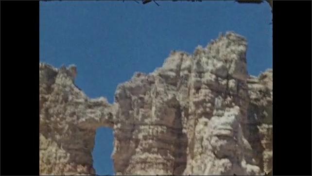 1940s: Rock spires with blue sky. Pine trees with pinnacles behind. Cliffs. Hoodoos and sand rock, wind blows on pine tree. Row of pinnacles.