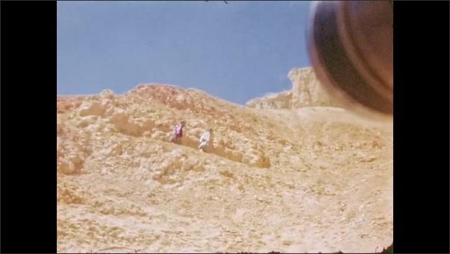 1940s: UNITED STATES: men walk along track in desert. Men climb up slope. Men wave at camera