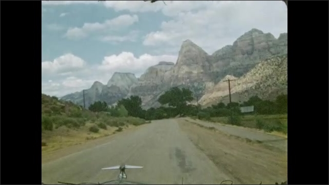 1940s: UNITED STATES: view of mountain road through window of car. Mountains around valley. Zion sign above road