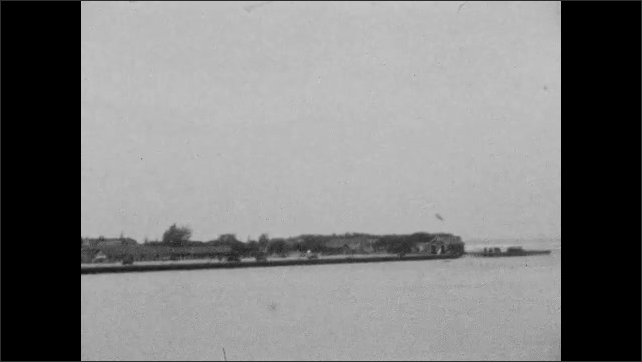 1920s: Scan of shoreline from boat of buildings and marine infrastructure. Person wades knee-deep in ocean.