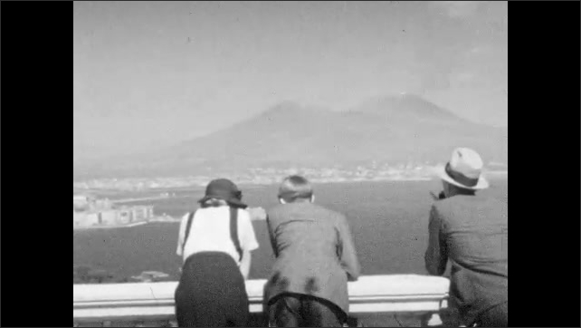 1930s: ITALY: EUROPE: couple enjoy view across Naples. People admire city view from balcony.