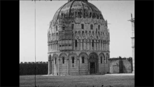 1930s: ITALY: EUROPE: Leaning Tower of Pisa. Dome in Italy. Boy stands by railing for photo. Boy looks over rails