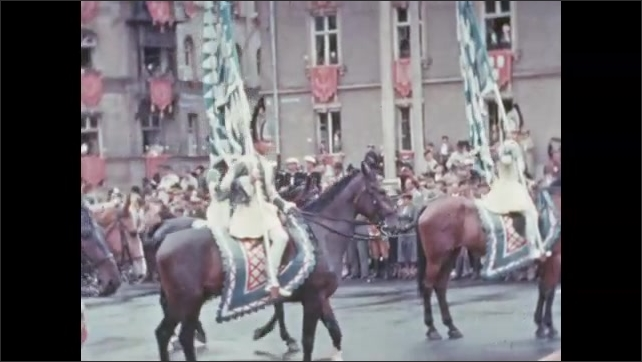 1930s: Soldiers in Hessian uniforms march in city parade. Hessian soldiers ride horses in parade. Ornate fountain on parade float. Women in costume dresses march in parade.