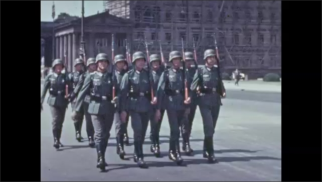1930s: Nazi soldiers march below memorial arch on street. Horsemen and soldiers march down street in military parade.