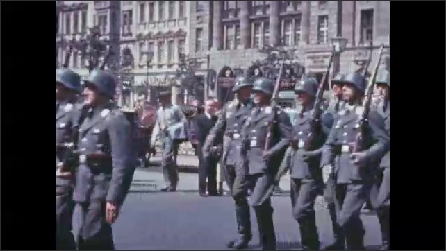 1930s: Horsemen and soldiers play instruments and march down street in military parade. Family gathers and talks near home.