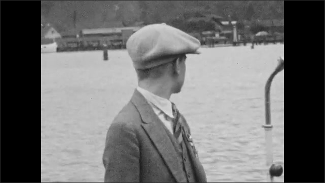 1920s: Teen girl in traditional Swiss dress adjusts lapel pin of teen boy on sidewalk. Woman in pinafore on street. Teen boy in cap and pins next to lake. Close-up of lapel pins. Buildings lakeside.