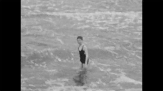 1920s: Boy jumps and swim in waves. Woman in bathing suit and cap walks down wharf with small dog. Boys climb on wooden dock in water.