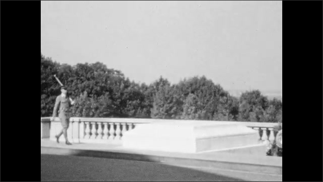 1920s: A man with a hat stands on porch stairs. Man walks in front of building. Guard on patrol. Washington monument seen from Lincoln memorial.
