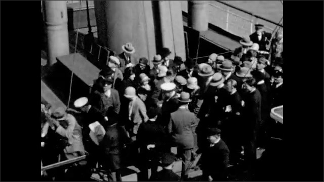 1920s: People crowd as they leave ship. Man stands on deck and waves. Man stands at railing on deck.