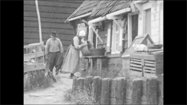 1920s: People in front of store. Children walk on street. Woman walks, smiles. Woman holds bucket outside while a woman enters house, man walks by. Woman washes clothes at canal. Boats move on canal.