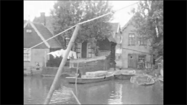 1920s: Crowd of people walks along canal with houses. Rowing boats at dock in canal with houses in background. People walk. Houses by canal with clothes that hang on a rope.
