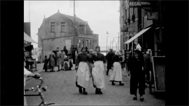1920s: Two girls walk on street and knit, street vendor pushes cart behind. People stand on busy town street, man mounts bike, women walk arm in arm, man smokes pipe, woman walks by and smiles. Dock.