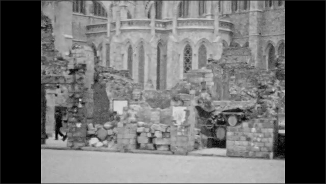 1920s: Facade of St. Martin's Cathedral in Ypres. Facade of Cathedral. People walk in front of Cathedral. Columns on the ground and scaffolding in front of building under construction.