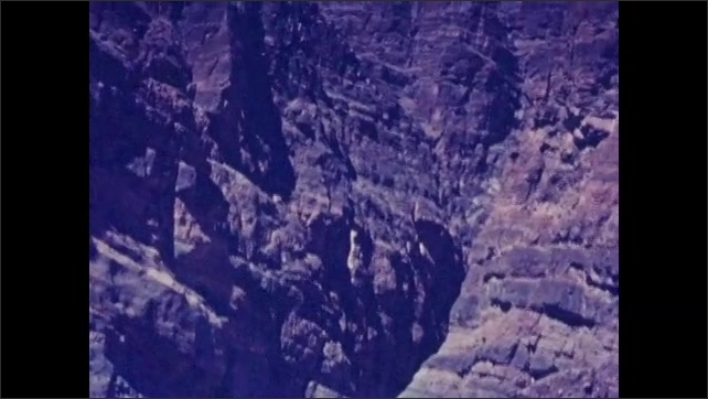 1920s: UNITED STATES: car drives at foot of mountains. Rock face in desert. Car visits mountain landscape